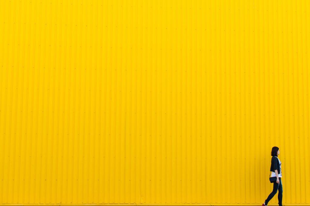 Frau vor gelber Wand